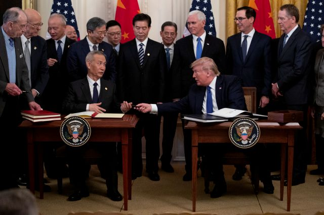 "In this Jan. 15, 2020, photo, President Donald Trump hands a pen to Chinese Vice Premier Liu He after signing ""phase one"" of a US China trade agreement, in the East Room of the White House in Washington. (AP Photo/ Evan Vucci)"