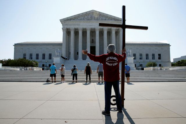 Tom Alexander holds a cross as he prays prior to rulings outside the Supreme Court on Capitol Hill in Washington, Wednesday, July 8, 2020. The Supreme Court is siding with two Catholic schools in a ruling that underscores that certain employees of religious schools, hospitals and social service centers can't sue for employment discrimination.(AP Photo/Patrick Semansky)