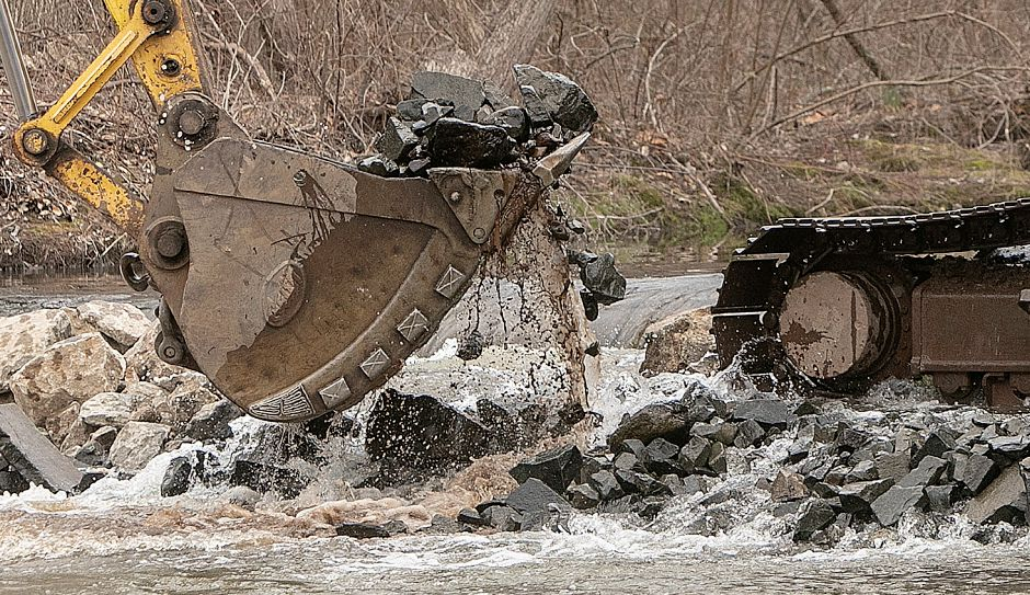 An excavator scoops up rock Friday as part of a project to remove a section of 30-inch pipe from the Quinnipiac River in Meriden. Dave Zajac, Record-Journal