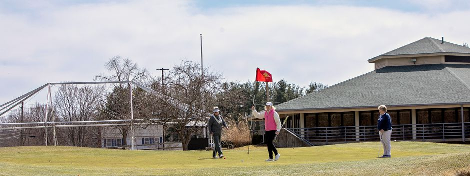 Myra Reynolds, of Southington, center, pulls the pin on Hole 18 while finishing up a round of golf with Cheryl Perito, of Old Saybrook, left, and Mara Dunleavy, of Wallingford, right, at Hunter Golf Club in Meriden, Tues., Apr. 2, 2019. Meriden officials are considering adding a banquet hall to the municipal golf course. The course currently uses a seasonal tent, left, next to Violi