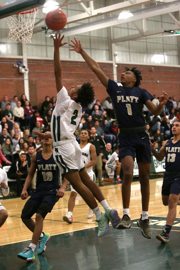 Maloney's Rashawn Wilson goes up for a shot as Platt's Jher'quez Slater defends during Friday's rivalry game at Maloney. The Spartans held on for a 73-68 victory. | Emily J. Tilley, Special to the Record-Journal.