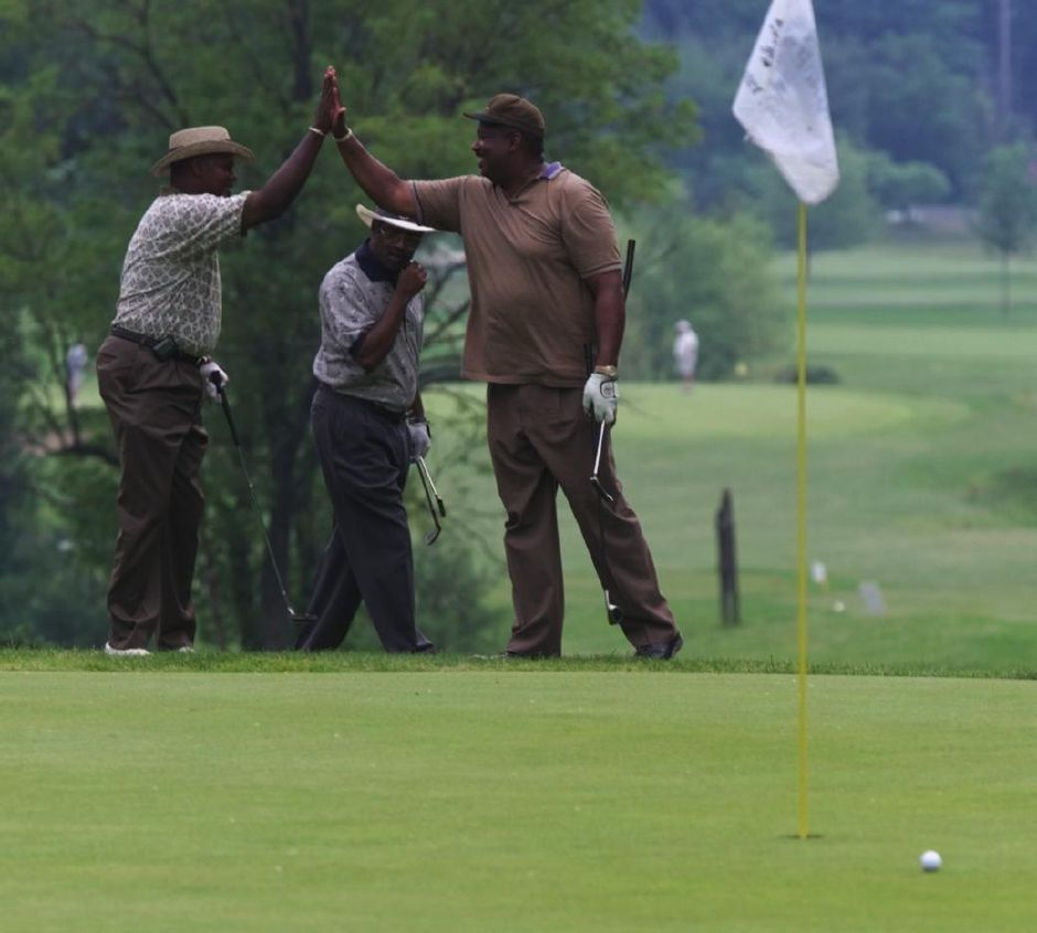 James gatling, left, gives a high five to Dave Gilmore, after Gilmore came very close to sinking a long putt at Hunter Memorial golf course in Meriden, during the Meriden Chamber of Commerce golf tournament June 2, 1999. Roger Gaston is walking in the background. They are all from Waterbury, and are with the Community Action Agency of Meriden. The forth person in the group was Greg Weathers.