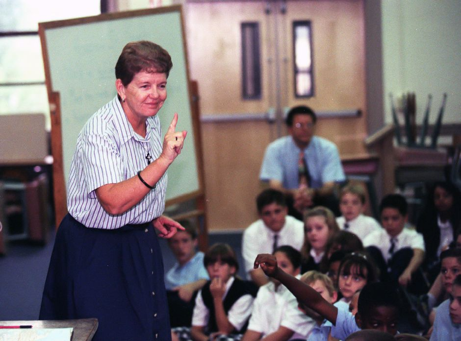 IN OUR SCHOOLS: Sister Mary Ellen Flynn, a missionary nun , talks to an assembly of St. Joseph School students Friday Sept. 10, 1999 about her experiences in Haiti. In the photo she relates that the typical home in Haiti is just one room.