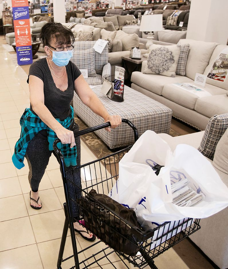 Denise Bachand, of Newington, heads for the exit after purchasing a variety of merchandise at Boscov's at the Westfield Meriden mall, Thurs., May 21, 2020. Boscov's department store reopened at 11 a.m. with reduced hours and new safety precautions. Dave Zajac, Record-Journal