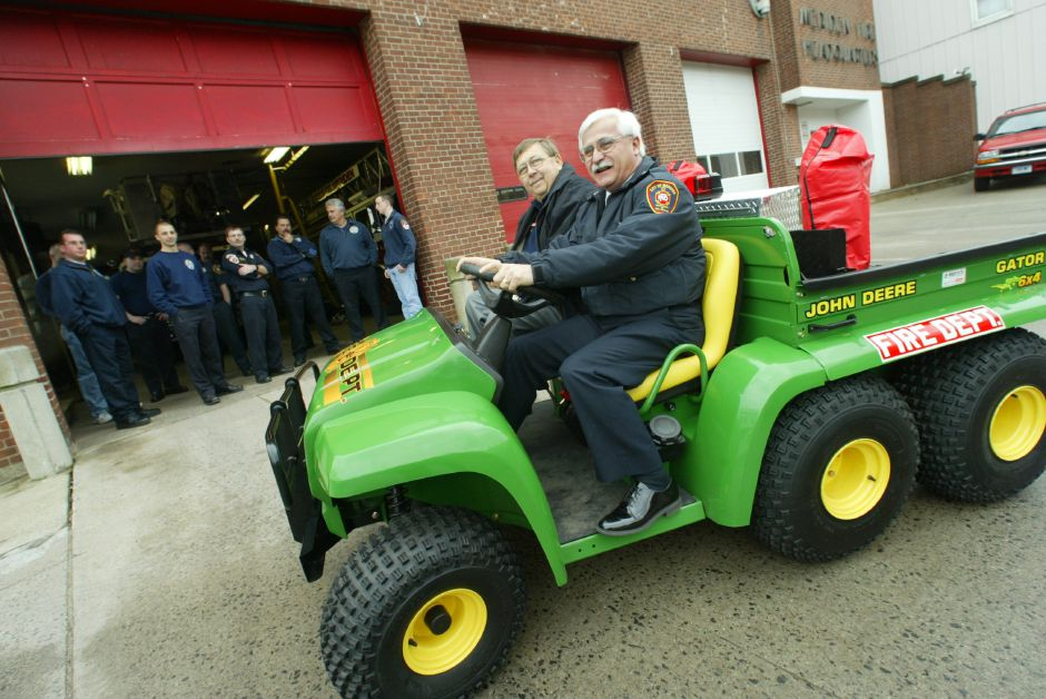 FILE PHOTO: Former Meriden Fire Chief James Trainor at the wheel of a 2004 John Deere Gator 6x4 vehicle donated by Geoffrey Nielsen of Wethersfield sitting in the passenger seat in front of the Pratt Street fire station Friday morning March 5, 2004.