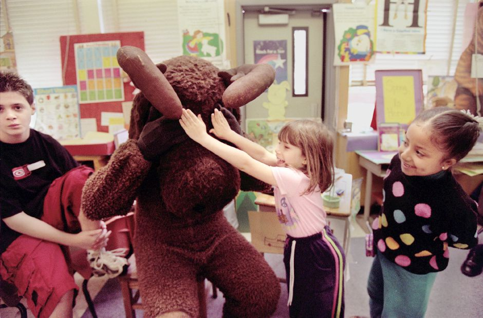 "First grader Catherine Freitas plays a Joke on "" Morris the Moose"" by covering his eyes while surrounded by other students including Lou Faiella, III (left), 13 ( who visited the class with his dad) and first grader Olaya Cazorla ( far right). Lou Faiella, Jr, a student-teacher at Cooke Hill School , dressed up as "" Morris the Moose"" ( a character from the B. Wiseman children"