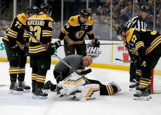 Boston Bruins goaltender Tuukka Rask (40) is attended to by medical personnel as his teammates look on after taking a hit on a goal by New York Rangers center Filip Chytil during the first period of an NHL hockey game, Saturday, Jan. 19, 2019, in Boston. (AP Photo/Mary Schwalm)
