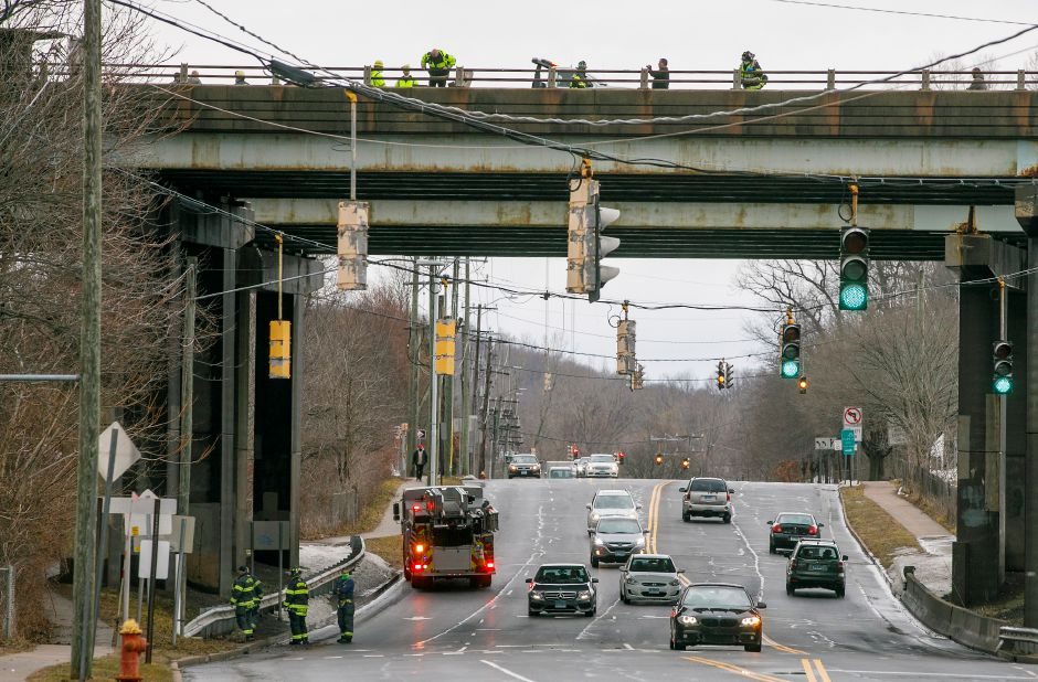 Meriden firefighters, bottom left, check the area where debris came down along Lewis Avenue after a dump truck overturned on Interstate 691 eastbound, March 1, 2021. Emergency service crews, above, look down to Lewis Avenue from near the site of the crash. Dave Zajac, Record-Journal