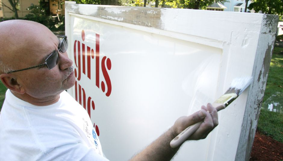 Salvatore DiCostanzo, an employee of Cytec, paints the main sign in front of Girls Inc. on Lincoln St. in Meriden on Wednesday, Sept. 12, 2007. A large group of volunteers from Bristol Meyers Squibb and Cytec were helping with various projects at Girls Inc. during the Meriden-Wallingford United Way Day of Caring.