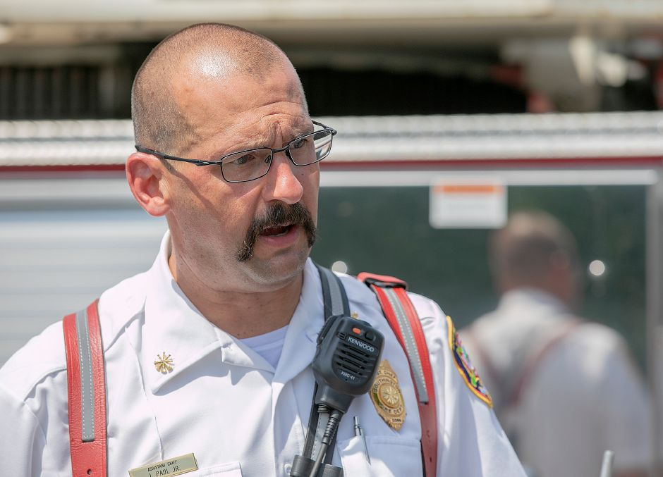 Southington Assistant Fire Chief James Paul, Jr., talks on the scene of a house fire at 354 Clark St. in Southington, July 17, 2019. Dave Zajac, Record-Journal