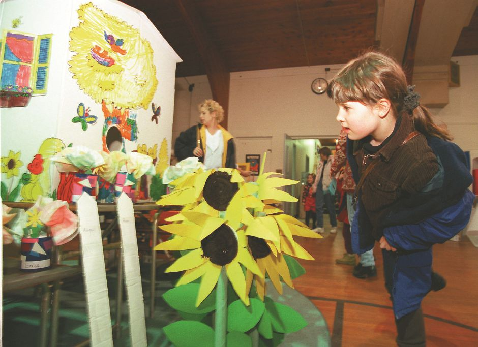 RJ file photo - Kaitlyn McNulty, 7, looks for the flowers her sister, Courtney, made for the Girls Inc. preschool program. The preschool transformed its Lincoln Street building into a gallery to display art and science projects March 19, 1998.