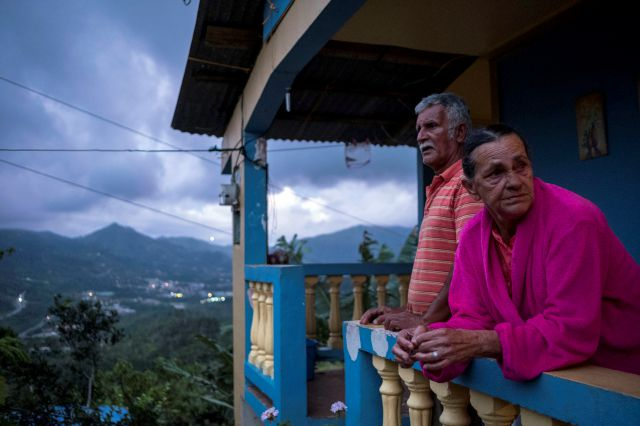In this July 12, 2018 photo, Marta Bermudez Robles and her husband Juan Nunez stand on the balcony of their home which is still without power since Hurricane Irma and Maria in Adjuntas, Puerto Rico. With the expected, soon to come restoration of power to their home, Bermudez said she planned to celebrate no longer having to eat a diet of mostly rice, bananas and soup, or wash clothes by hand in a sink that they found on the street after Hurricane Irma. (AP Photo/Dennis M. Rivera Pichardo)