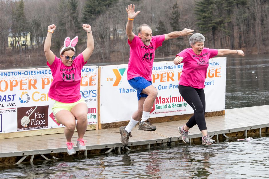 "Left to right: Kelly Cozzolino, Bill Cozzolino, and Terri Connellan, introduced as the ""Y picture lady"", jump into the Sloper pond during the 15th annual Sloper Plunge, in Southington, January 18, 2020. The event by the Southington-Cheshire Community YMCAs raises money for local kids to attend camp. Photo by Derek Torrellas, special to the Record-Journal."