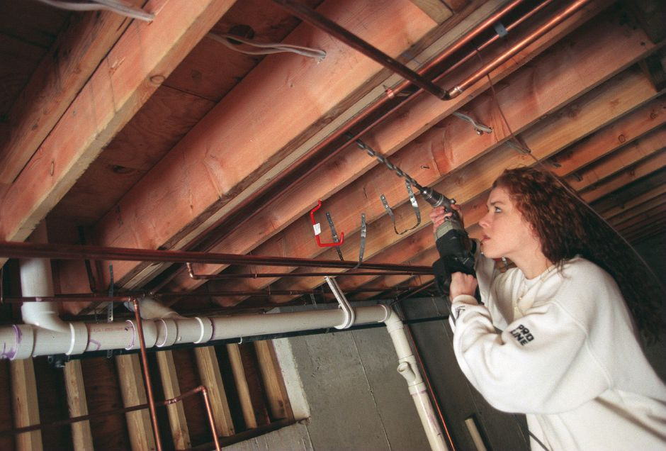 RJ file photo - Krissy Voisine, a student at Wilcox Regional Technical High School in Meriden, drills a hole to run a thermostat wire to the heater in the basement of a house being built at 750 Center St. in Wallingford for Habitat for Humanity, March 1999.