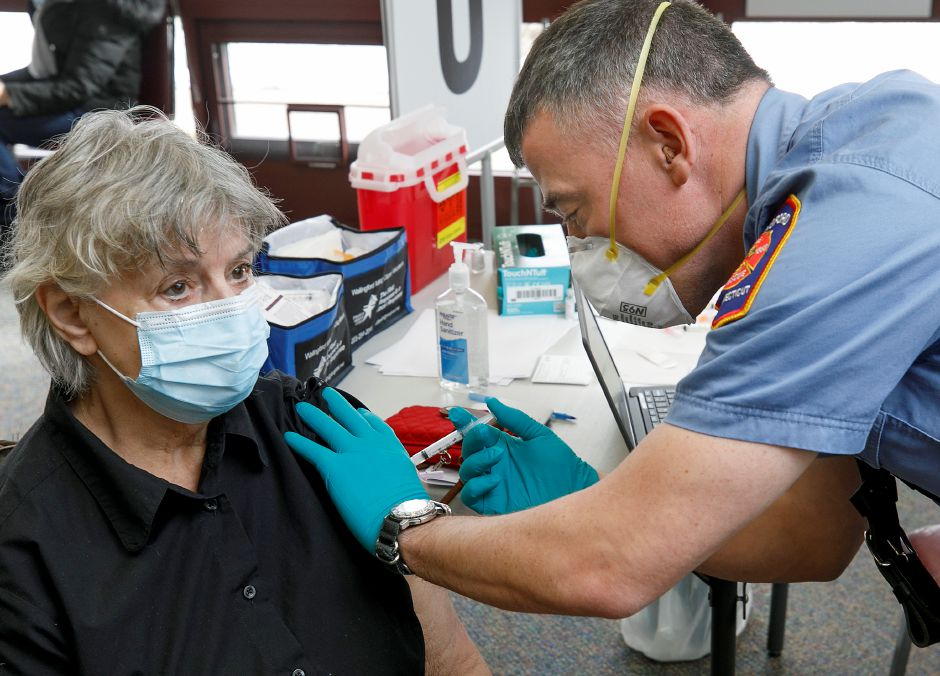 Wallingford Fire Department EMS Lt. Michael Krupinski administers the COVID-19 vaccine to Gail Morse, of Wallingford, at the Wallingford Senior Center, Thurs., Jan. 28, 2021. Dave Zajac, Record-Journal