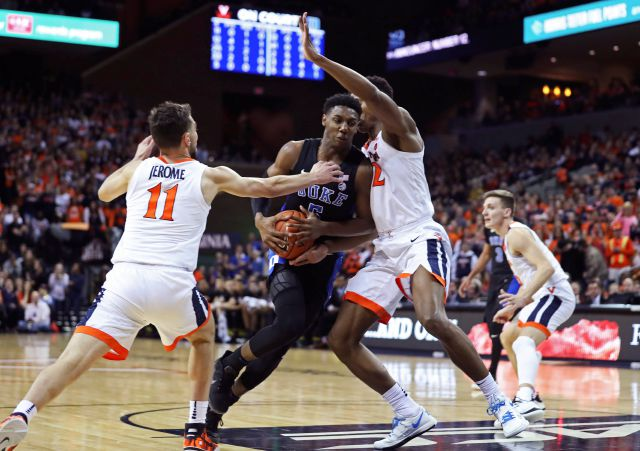 Duke forward RJ Barrett (5) splits two Virginia defenders during the first half of an NCAA college basketball game Saturday, Feb. 9, 2018, in Charlottesville, Va. (AP Photo/Zack Wajsgras)