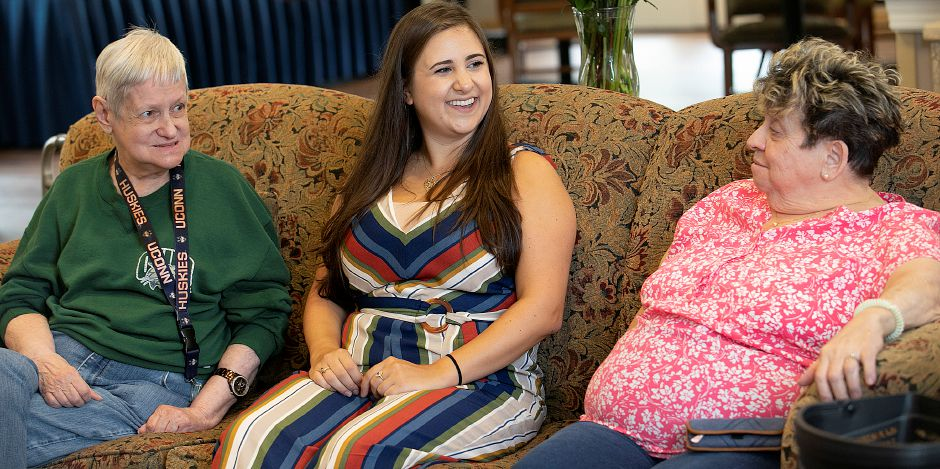 Quinnipiac University graduate student Julia Kowal visits with residents Alice Leighner, left, and Yolanda Ruggiero at Ashlar Village in Wallingford on Wednesday.