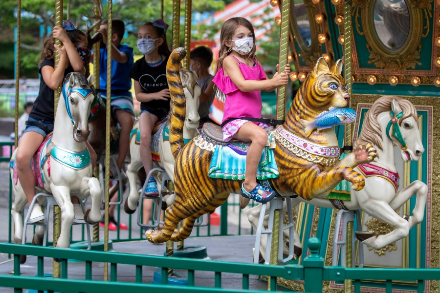 Olivia Swaynn, 5, of Newington rides a cat on the Kiddie Carousel at Lake Compounce in Bristol on Tuesday. Visitors must wear a mask throughout the park and on rides and will be seated by ride attendants for proper distancing. Photos by Aaron Flaum, Record-Journal