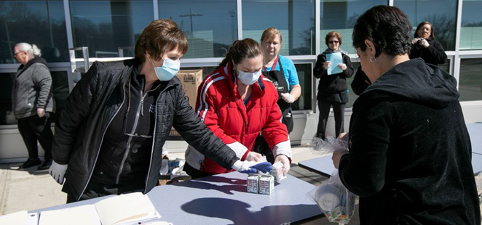 Meriden schools cafeteria workers wear masks while distributing food to families at Lincoln Middle School, Mon., Mar. 16, 2020. Dave Zajac, Record-Journal