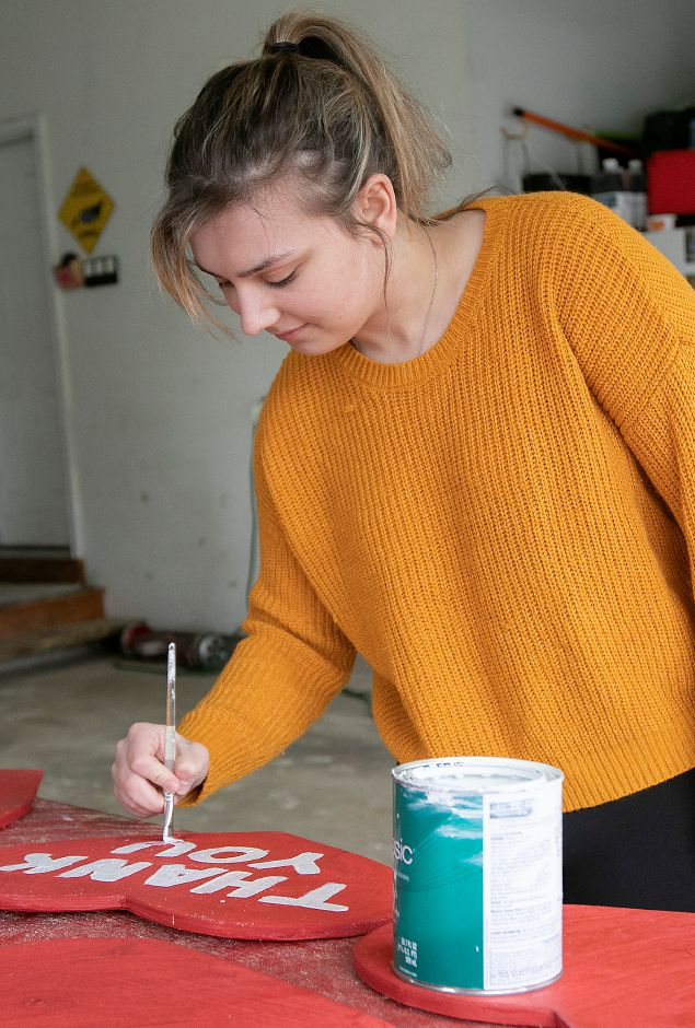 Mikayla Wollen, of Wallingford, paints a thank you on one of the many signs her family is creating and selling to donate snacks for local hospitals and nursing homes, Mon., Apr. 27, 2020. Dave Zajac, Record-Journal