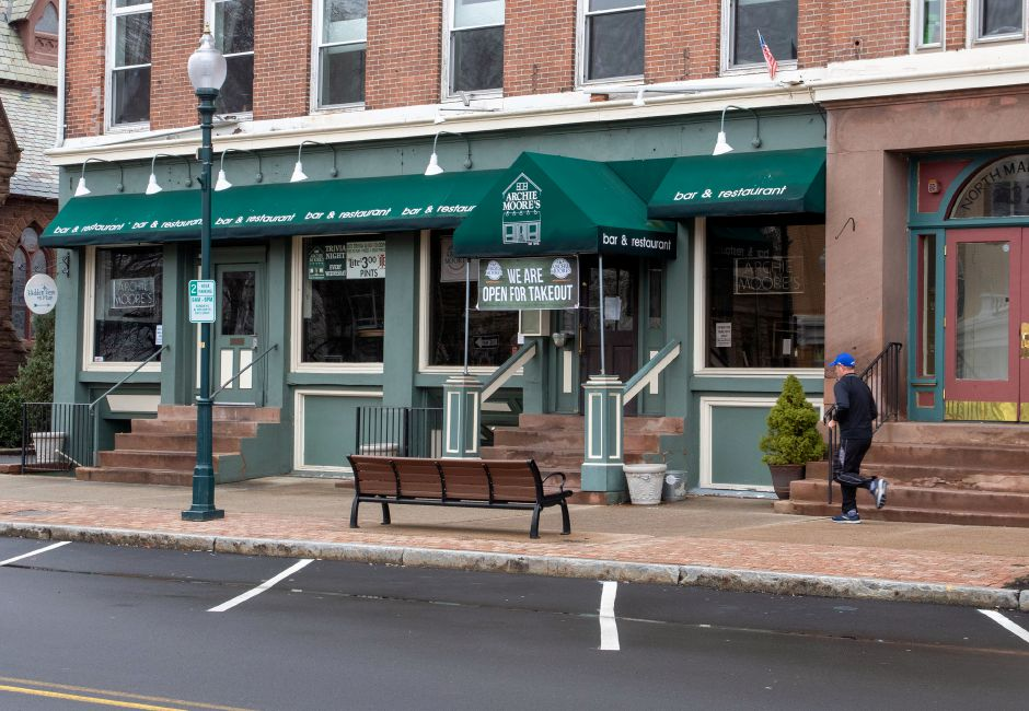 A jogger runs up North Main Street in front of Archie Moore'ss as there is plenty of parking along North Main Street in Wallingford around lunchtime on Thursday, March 19, 2020. Aaron Flaum, Record-Journal