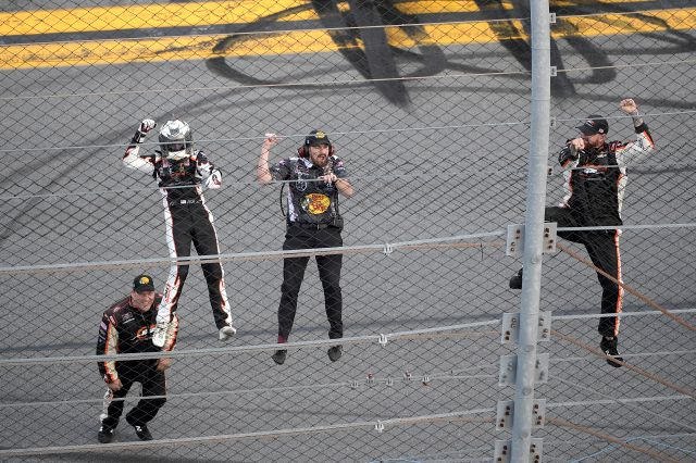 Noah Gragson, left, and crew members celebrate by climbing onto the grandstands safety fence after winning a NASCAR Xfinity series auto race at Daytona International Speedway, Saturday, Feb. 15, 2020, in Daytona Beach, Fla. (AP Photo/Phelan M. Ebenhack)