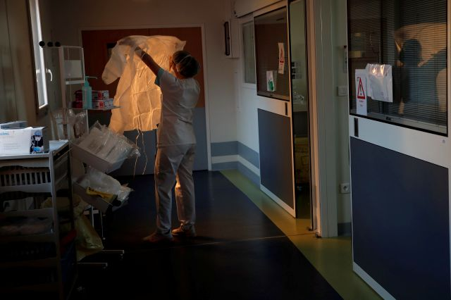 A medical worker prepares to tend to a patient affected with the COVID-19 in the Amiens Picardie hospital Tuesday, March 30, 2021 in Amiens, 160 km (100 miles) north of Paris. (AP Photo/Francois Mori)