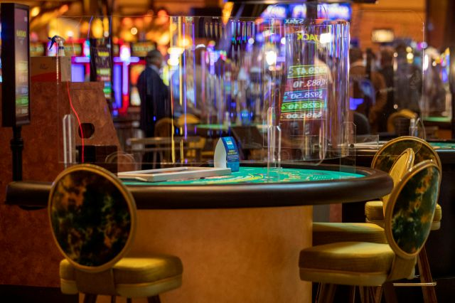 Plexiglass separates guests from each other and the dealer at the Black Jack tables at the Mohegan Sun casino, Thursday, May 21, 2020, in Uncasville, Conn. Connecticut