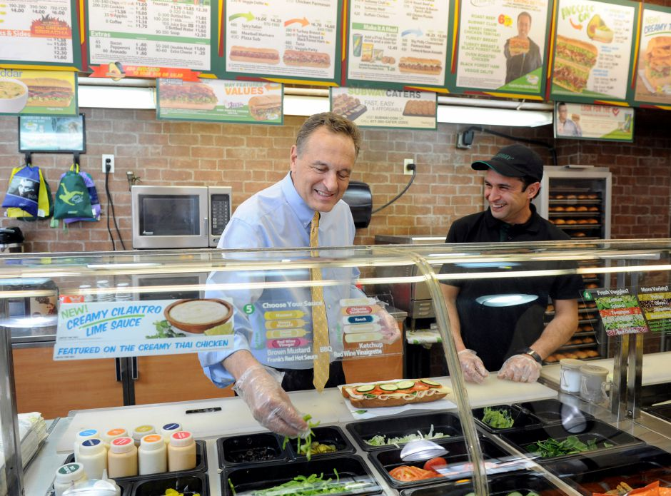 Fred DeLuca, left, Co-Founder and CEO, SUBWAY Restaurants, gets to work behind the counter at a SUBWAY store in New York, Tuesday, May 6, 2014. (Diane Bondareff/Invision for SUBWAY/AP Images)