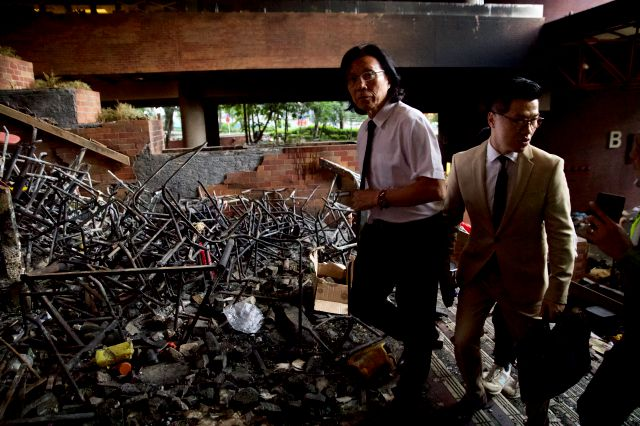 Gary Fan Kwok-wai, lawmaker and newly elected district councillor, right, and lawyer Wong Kwok Tung, left, walk through burned debris as they try to meet with the trapped protesters at the Polytechnic University in Hong Kong, Monday, Nov. 25, 2019. Hong Kong