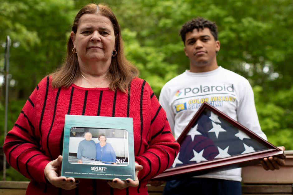 Florence Hopp  holds a photograph of herself and her husband Robert Hopp as her son J.J. Brania-Hopp holds the  flag the military presented to them after Hopp's death. Hopp was one of at least 79 residents of a veterans home in Paramus, New Jersey, to die from COVID-19. Mary Altaffer, Associated Press
