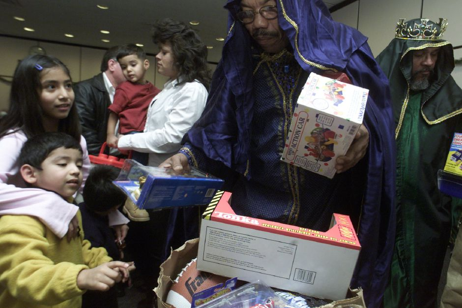 (L) Jorge Perez, 4, and his sister Adriana Perez, 10, wait for a gift from one of the Three Kings, played by Justo Rios, Sunday at the Meriden Public Library Jan. 7, 2001. Jorge chose a Powere Ranger action figure during the Three Kings celebration. The St. Rose Hispanic Choir provided the entertainment for the afternoon.