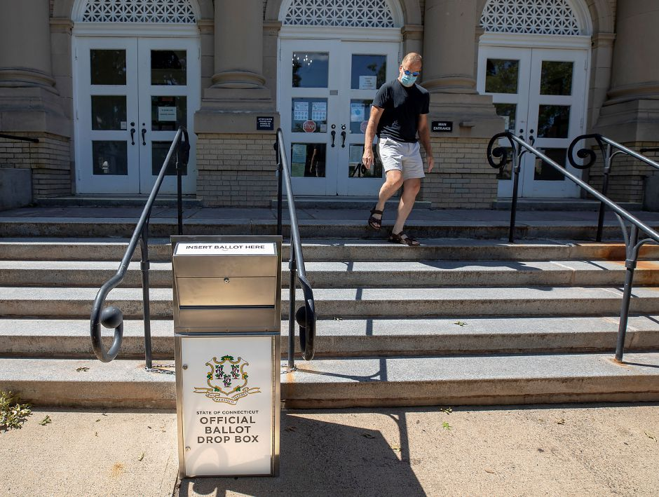 Jon Birney walks by an official ballot box in front of Wallingford Town Hall. Public Works crews installed two absentee ballot drop boxes outside Town Hall Monday, after a back-and-forth between the mayor and the state about drop box accessibility.