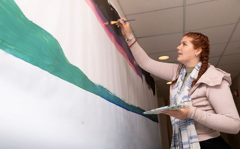 Artist Kelly Triolo paints a landscape on a banner for the downtown preservation and development conference in Meriden, Wed., Nov. 13, 2019. The Making Meriden Business Center in partnership with CT Main Street Center, the city and others will host the preservation and development conference Thursday at the Silver City Ballroom, 16 Colony St. Dave Zajac, Record-Journal