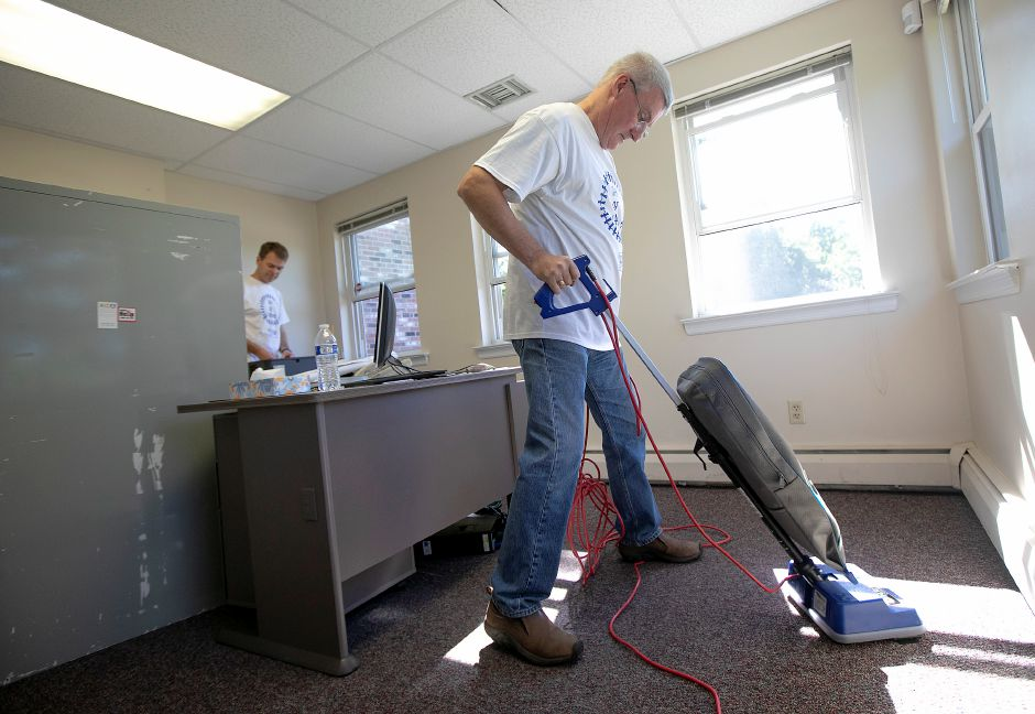 Mirion Technologies employees Jim Zickefoose, left, and Mark Smith clean up an office after painting while volunteering at the Child Guidance Clinic in Meriden as part of the United Way's Day of Caring Tuesday. Dave Zajac, Record-Journal