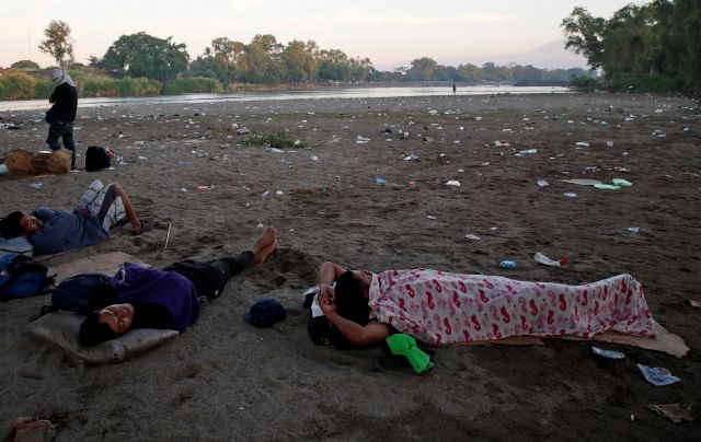 Central American migrants sleep on the bank of the Suchiate River in Tecun Uman, Guatemala, across the river from Mexico, at sunrise Tuesday, Jan. 21, 2020. Hundreds of Central American migrants are stranded in a sort of no-man's land on the river border between Guatemala and Mexico after running up against lines of Mexican National Guard troops deployed to keep them from moving en masse into the country and on north toward the U.S. on Monday. (AP Photo/Moises Castillo)