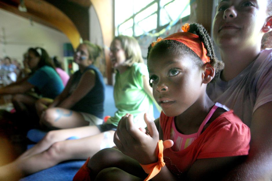 Eryka West, 5, (CQ) sits clapping in the lap of Tomisyn Mack (CQ), Co-Director of Life Guarding as they watch the week ending performance from the various age groups at Girls Inc. Summer Camp in Meriden Friday afternoon, Aug. 3, 2007.