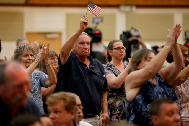 Supporters of Rep. Elaine Luria, D-Va., wave flags and applaud during a town hall at a church in Virginia Beach, Va., Thursday, Oct. 3, 2019. Luria recently joined a group of other Congresswomen to call for the impeachment of President Trump. (AP Photo/Steve Helber)