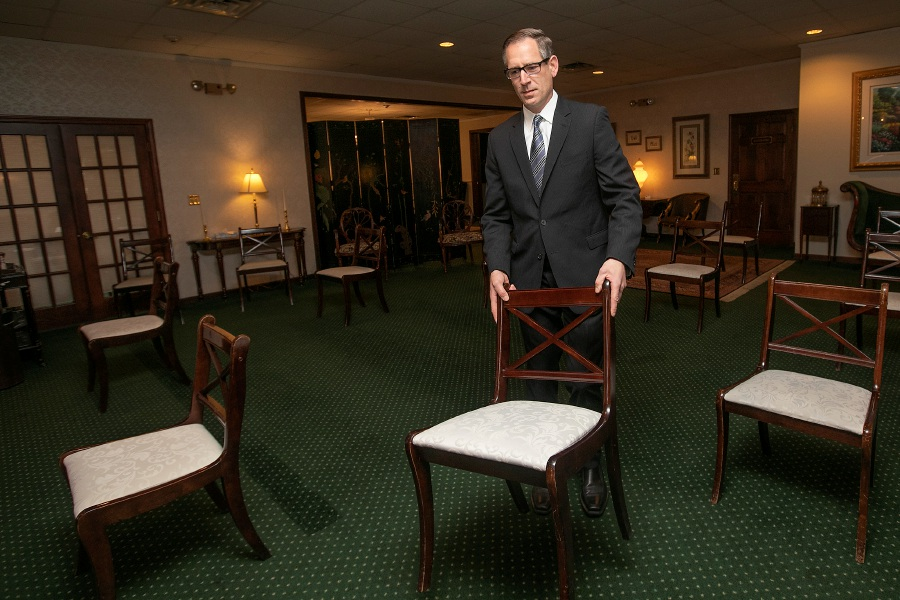 David Warren MacDonald, funeral director, arranges chairs for social distance in a gathering room at Wallingford Funeral Home in Wallingford on Monday. Dave Zajac, Record-Journal