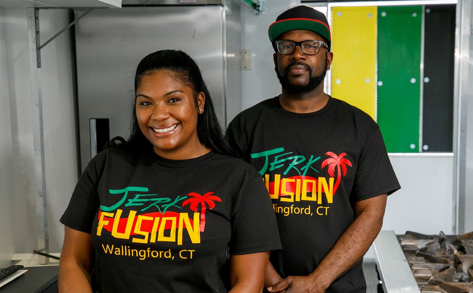Jerk Fusion owner Enjoli Hassan, of Meriden, and business partner Glendon Roberts stand in the kitchen of the Jamaican-fusion cuisine food truck stationed in the Wallingford Commons plaza across the street from Kohl
