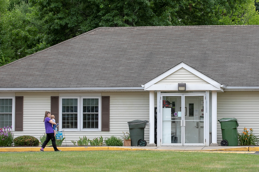 A woman carries a child into the Masonic Child Development Center in Wallingford, Fri., Jul. 10, 2020. The Wallingford Family YMCA is slated to take over management of the Masonic Child Development Center. Dave Zajac, Record-Journal