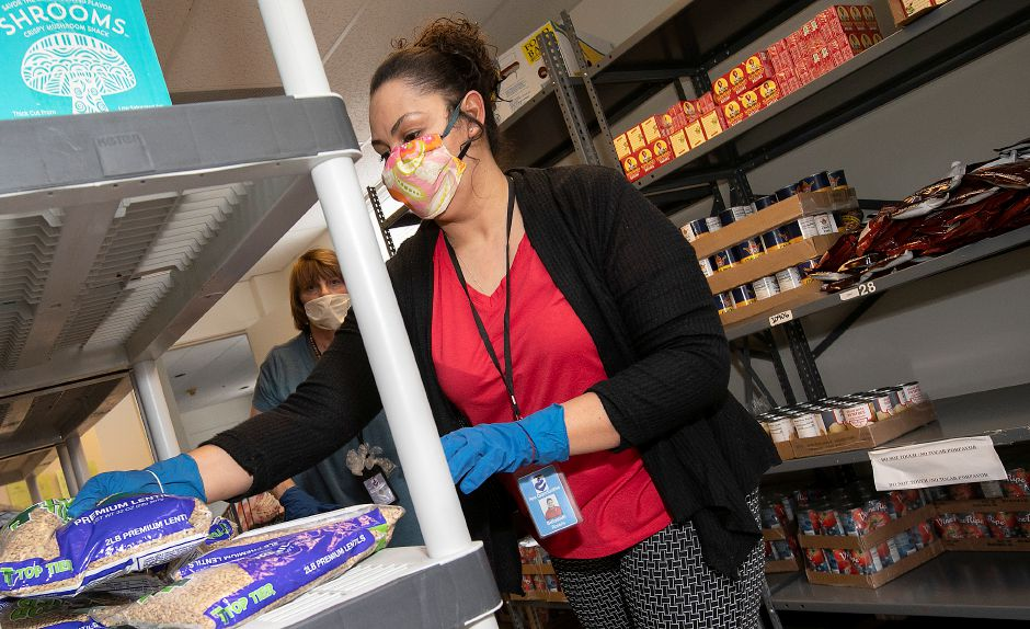 New Opportunities Inc. of Greater Meriden Case Manager Beth Rosario and Director Dona Ditrio stock shelves with food items in the pantry of the non-profit, Tues., Apr. 14, 2020. Dave Zajac, Record-Journal