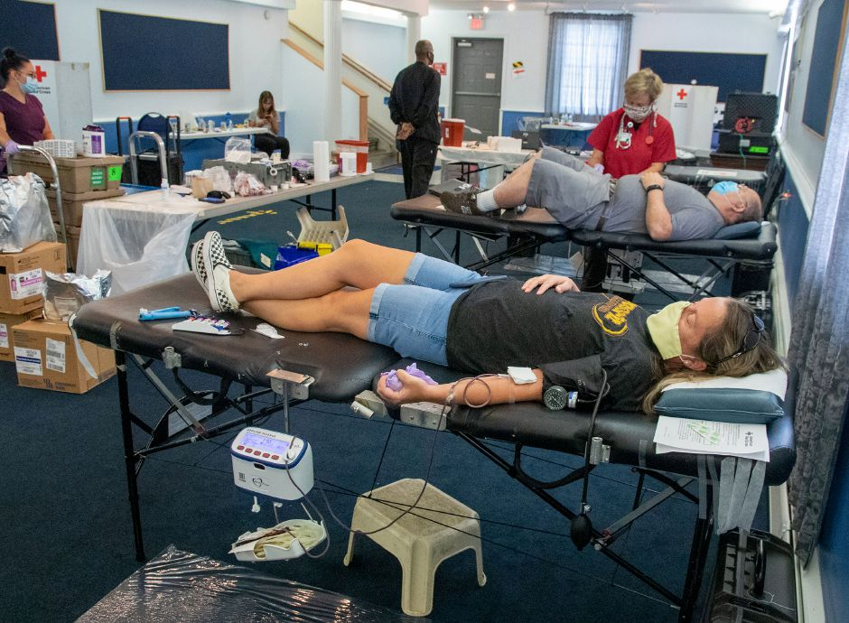 Elaine Villano of Wallingford lays on a table as blood as she donates blood as American Red Cross' Barbara Kamianowski checks on Gary Veloin of Waterbury during a blood drive at the Cheshire Masonic Temple Lodge in Cheshire on Friday, Sept. 11, 2020. Aaron Flaum, Record-Journal