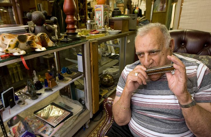 Frank Termini, 90, plays harmonica to country tunes on the radio while passing time between customers at Frank's Garage Sale at 18 S. Orchard St. in Wallingford. Termini, a WWII U.S. Navy veteran, had been operating the business for 35 years.