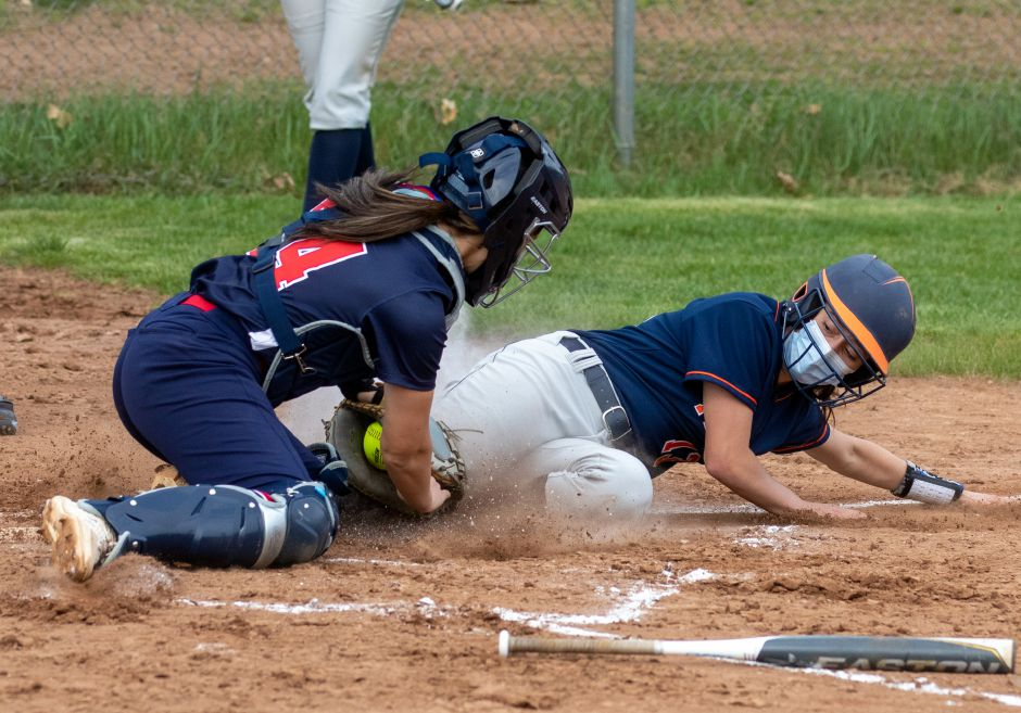 Lyman Hall's Emily Chase slides safely into home against Foran catcher Kendall LaMorte in a game earlier this season in Wallingford. The Trojans have made aggressive baserunning a staple of their season.  Aaron Flaum, Record-Journal