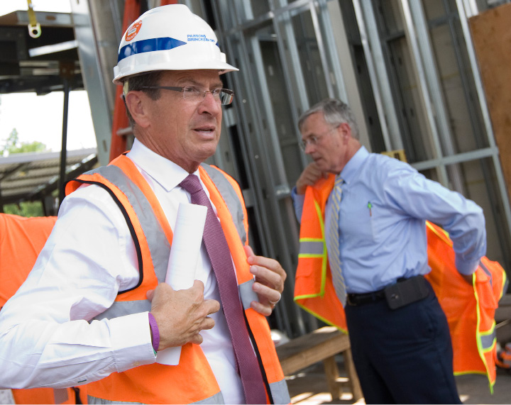 Governor Dannel P. Malloy and DOT Commissioner James Redeker put on construction vests before a tour of the Wallingford train station, Wednesday, July 6, 2016. Malloy provided an update on the Hartford Line expected to be completed by January 2018.  | Dave Zajac, Record-Journal