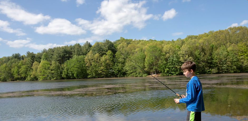 Joseph Guarnieri, 9, of Wolcott, tries his luck fishing while visiting Camp Sloper Friday.
