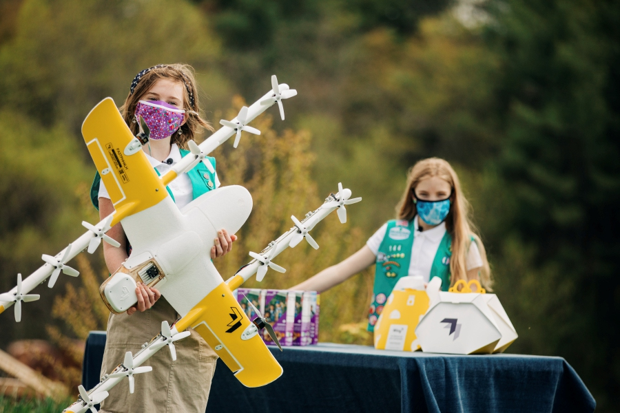 In this April 14, 2021 image provided by Wing LLC., Girl Scouts Alice, right, and Gracie pose with a Wing delivery drone in Christiansburg, Va. The company is testing drone delivery of Girl Scout cookies in the area. (Sam Dean/ Wing LLC via AP)