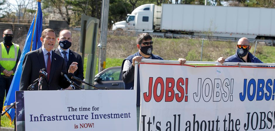U.S. Sen. Richard Blumenthal speaks next to Mayor Kevin Scarpati in support of President Joe Biden's American Jobs Plan during a press conference held in the commuter lot on Bee Street near interstates 91, 691 and Route 15 in Meriden, Mon., Apr. 19, 2021. A $300 million plan to improve the convoluted traffic triangle at the junction of interstates 691, 91 and Route 15 has been divided into three phases. At right, New England Regional Council of Carpenters representatives, David Jarvis, left, and Jason Lebel hold a sign in support of the project. Dave Zajac, Record-Journal