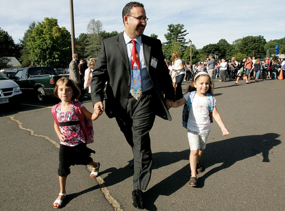 Record Journal Photo/ Johnathon Henninger 8.27.08 - left to right, Caitlyn Hart, 6, walks with Hanover Principal, Miguel Cardona who also holds the hand of Bridget Ruiz, 5 years old. Both girls are begining their first day of first grade together Wednesday morning at Hanover School in Meriden.
